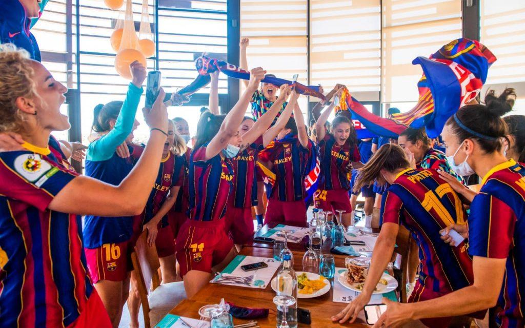 Jogadoras do Barcelona festejam título da Primeira Iberdrola ao redor de uma mesa com comes e bebes.